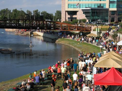 Promenade sur la coulée verte Downtown River Greenway, bordée de stands d'exposition et de nourriture