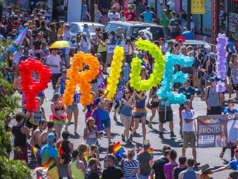 Foule portant des ballons colorés lors de la parade Pridefest à Denver