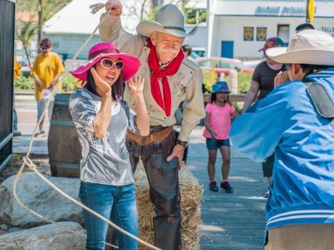 Femme posant aux côtés d'un cowboy durant le Santa Clarita Cowboy Festival en Californie
